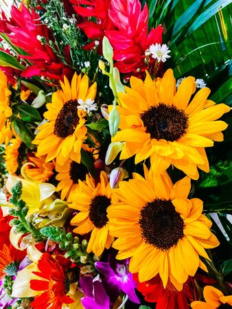 Bouquet of flowers, close-up composition of a bouquet of flowers, red roses, sunflowers, green leaves. Flower decoration, gift for women's day, wedding, birthday. Floral design.