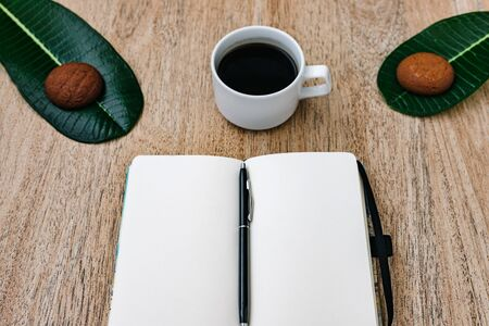 Flat lay, open blank U-turn of a notepad with white paper, morning recording of plans, breakfast with aromatic coffee and chocolate chip cookies. Composition on a light wooden background, place for text and insert. Copy place. Stock Photo