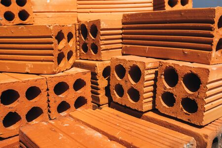 Hollow red bricks piled in a pile, ready for use in construction or for sale. Construction material. Neatly folded brick, photo for advertising. Copy place