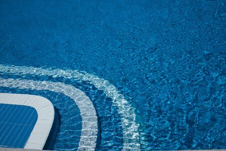 Steps to the pool, blue clear water in the outdoor swimming pool, safe descent to the pool, close-up steps through the water. White steps on a blue background, good shape, visibility. Ripples on the surface of the water. Copy place
