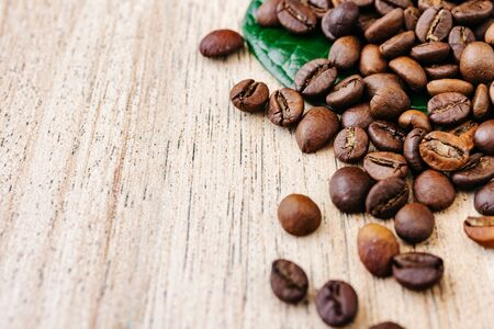 Coffee beans on a green leaf and scattered on a light wooden table, fragrant fried beans for freshly americano, espresso, natural background, top view, closeup grains, flat lay, place to insert text, copy space