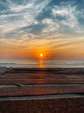 Dawn on the sea with a view of the horizon, colorful sky from the sun rays, clouds on a blue sky. Sandy beach on the seashore, waves on the sea, copy place
