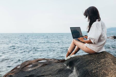 Young successful girl working using a laptop, sitting on a rocky seashore. Business woman working on remote work while traveling, blogger, freelancer, compiles content plan, work online