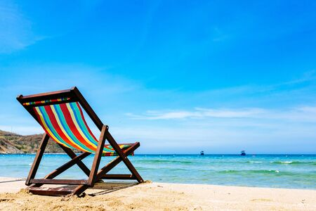 One deck chair on a sandy tropical beach with clear sea, bruise color of water and blue sky on the background. Boats on the horizon in the sea. Copy place