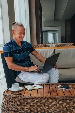 A young smiling guy is reading mail on a laptop, sitting in a spacious cafe with a cup of coffee. The student makes a note. Types the text of the message to reply Banque d'images