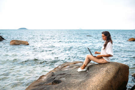 Young successful girl working using a laptop, sitting on a rocky seashore. Business woman working on remote work, freelancer, work online. Beautiful seascape in the background. copy space