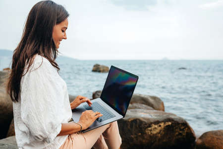 Freelance concept. A freelancer Smiling girl with a laptop on her lap works out of the office while sitting on a rock near the sea. Remote work in the fresh air, modern worker. Copy space
