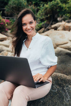 Young successful, smiling girl working using a laptop, sitting on a rocky seashore. Business woman working on remote work while traveling, blogger, freelancer, compiles content plan, work online. copy space Foto de archivo