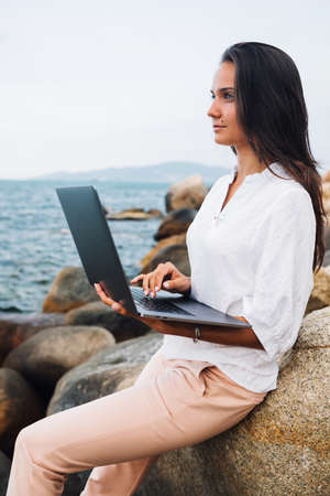 Young successful, girl working using a laptop, on a rocky seashore. Business woman working on remote work while traveling, blogger, freelancer, compiles content plan, work online. copy space
