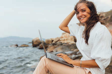 smiling girl working using a laptop, sitting on a rocky seashore. woman traveling, blogger, freelancer, compiles content plan, work online. copy space