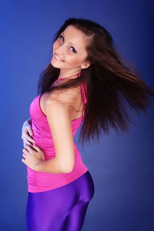 Belle jeune mannequin avec des cheveux sur fond bleu