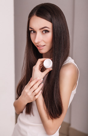 Skin Care. Beautiful healthy young woman with long hair, caring for their skin. Use cream for body care. Beauty and health.