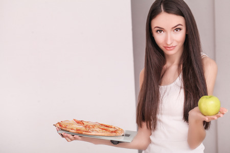 Diet. Young beautiful woman makes a choice between healthy lifestyle and harmful food. The concept of healthy eating and obesity. Beautiful slender figure girl.