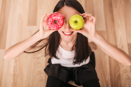 Diet. A young woman holding a pizza on the scales and make a choice between an apple and a donut. The concept of healthy eating. Stock Photo