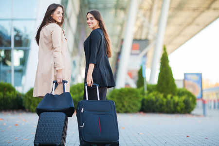 Vacation. Two happy girls traveling abroad together, carrying suitcase luggage in airport