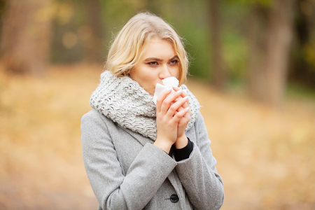 Girl sneezing in tissue. Young woman blowing her nose on the park. Woman portrait outdoor sneezing because cold and flu Stock Photo