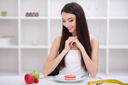 Diätkonzept. Junge Frau mit der Wahl zwischen Obst und Süßigkeiten