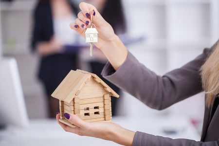 Salesman carrying a model house in hand is delivering the house key to the buyer,Customers receive home keys from home sales sales,Deliver house keys between seller and buyer.Home sales concept image