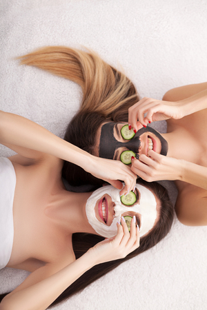 A picture of two girls friends relaxing with facial masks on over white background Zdjęcie Seryjne