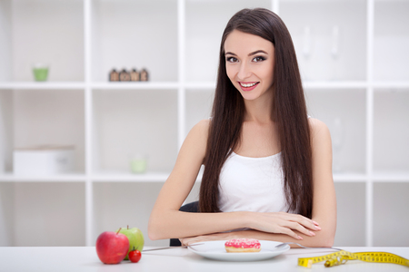 Dieting concept. Young Woman choosing between Fruits and Sweets