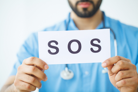 Health Care. Doctor Holding a Card With Symbol SOS, Medical Concept