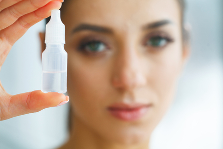 Vision And Medicine Concept. Young Girl Holds Eye Drops In Hands. Portrait of a Beautiful Woman with Contact Lenses. Healthy Look. High Resolution