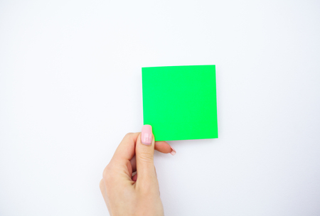Office Hand Holding a Green Color Sticker on White Background. Copyspace. Place for Text Banco de Imagens