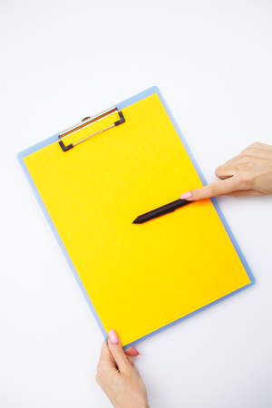 Blank Folder with Yellow Paper. Hand that Holding Folder and Handle on White Background. Copyspace. Place for Text