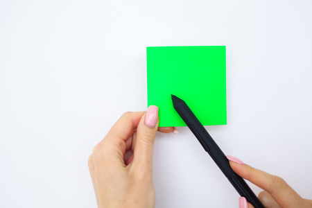 Office Hand Holding a Green Color Sticker and Pen on White Background. Copyspace. Place for Text