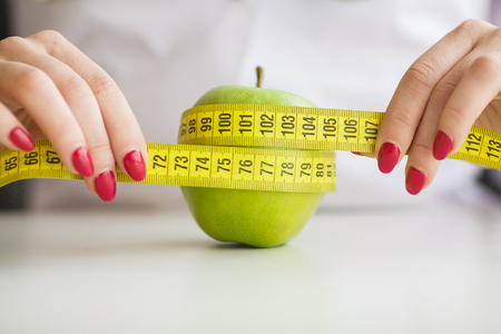 Diet. Woman holding a green apple and measuring Banque d'images - 114978317