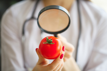 Diet Concept. Dietitian Inspecting Vegetables with Magnifying Glass