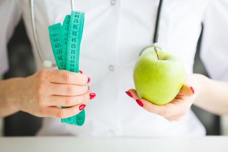 Diet. Female Nutritionist and Holding an Apple and a Measure Tape. New Start For Healthy Nutrition, Body Slimming, Weight Loss. Cares About Body