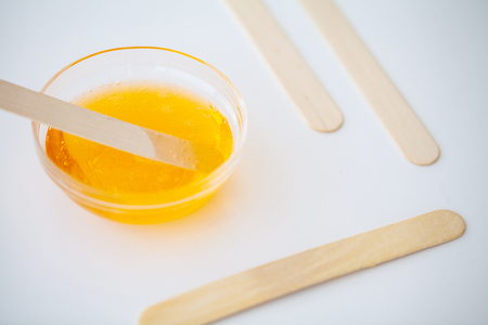Waxing. Paste for sugaring in beauty salon. Concept depilation with wax and sticks on white background top view.