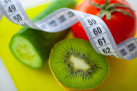 Diet or Weight Control Concept. Fruits and Vegetables With Measuring Tape On Weight Scale. Fitness and Healthy Food Diet Concept. 스톡 콘텐츠