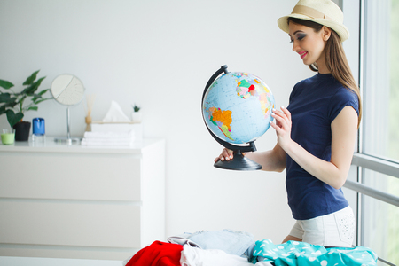 Vacation. Woman Who is Preparing for Rest. Young Beautiful Girl Sits on the Bed. Portrait of a Smiling Woman. Happy Girl Goes On Vacation Standard-Bild - 114978696