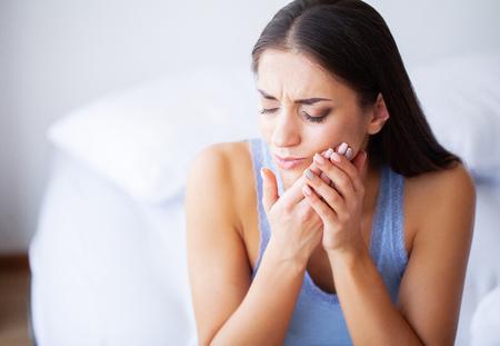 Zahnschmerzen. Frau, die Zahnschmerzen fühlt. Nahaufnahme des schönen traurigen Mädchens, das unter starken Zahnschmerzen leidet. Attraktive Frau, die schmerzhafte Zahnschmerzen fühlt. Zahngesundheits- und Pflegekonzept Standard-Bild