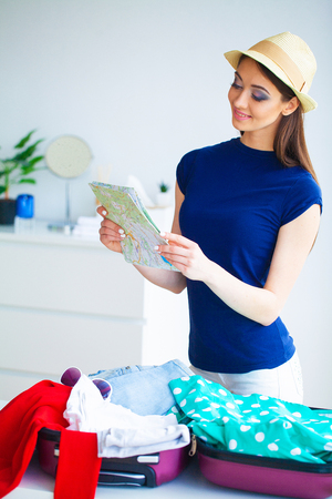 Vacation. Woman Who is Preparing for Rest. Young Beautiful Girl Sits on the Bed. Portrait of a Smiling Woman. Happy Girl Goes On Vacation Standard-Bild - 114979057