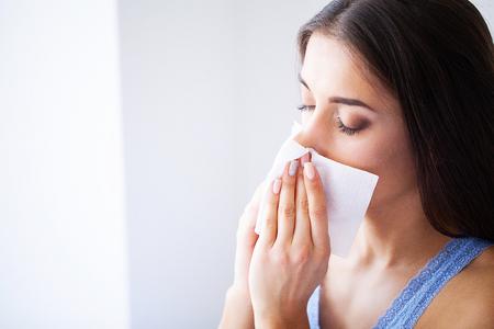 Griep en zieke vrouw. Zieke vrouw met papieren zakdoekje, hoofd koud probleem