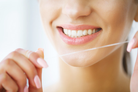Teeth Care. Beautiful Smiling Woman Flossing Healthy White Teeth. High Resolution Image Stock Photo