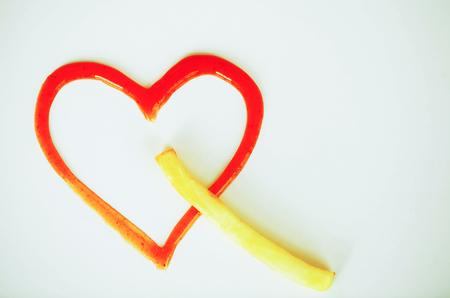 Diet. Heart of Ketchup. Golden Frost Potato on White Background.