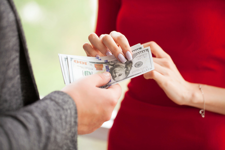 Business. Business Woman Gives Money to Men. Woman Dressed in Re