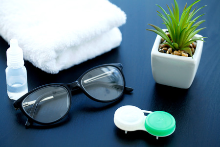 Glasses and objects for cleaning and storing contact lenses, to improve vision, on a black background