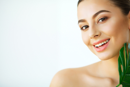 Skin Care. Beautiful Girl with Green Leaves. Beauty Treatment. Cosmetology. Beauty Spa Salon