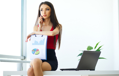 Business. Beautiful Young Woman Works on the Computer. Trims in Hands Phone. Bright Modern Office. Near Windows, Looks Happy and Smiles. High Resolution
