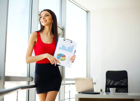 Business. Young Business Woman Standing Near the Big Window at the Office. The Girl Dressed in Red T-shirt and Black Skirt and Holding in Hands Blue Folder. The Girl Smiles.