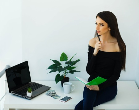 Office Business Woman Smiling and Sitting on the Table. Woman Dressed in Black Blouse and Blue Jeans. Work at Home. High Resolution