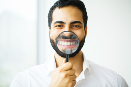 Businessman with magnifying glass zooming on his smile Stok Fotoğraf