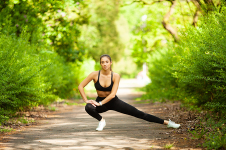 Fitness. Woman doing stretching exercise on park Foto de archivo - 114977796