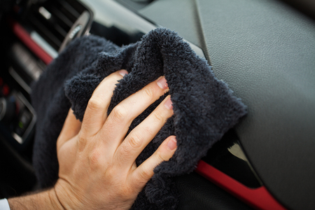 Cleaning car. Hand with microfiber cloth cleaning car interior Reklamní fotografie - 114978623