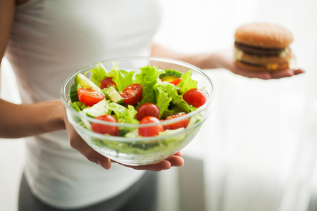 Diet. Woman Measuring Body Weight On Weighing Scale Holding Burger and Salat. Sweets Are Unhealthy Junk Food. Dieting, Healthy Eating, Lifestyle. Weight Loss. Obesity. Top View
